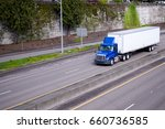 Small photo of A blue semi truck with day cockpit and a roof spoiler to reduce air resistance and improve aerodynamics carries the trailer with cargo along the road in an urban city area