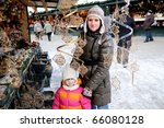 Young mother with amaze small daughter on christmas market in Europe - stock photo
