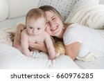 happy young mother lying on big ... | Shutterstock . vector #660976285