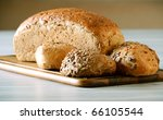 Composition with rolls and loaf of bread on breadboard - stock photo