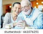 smiley senior couple watching... | Shutterstock . vector #661076251