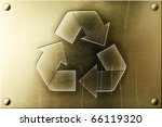 Recycling symbol on shiny yellow brass metal plate - stock photo