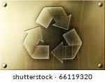 Recycling symbol on shiny yellow brass metal plate - stock photo