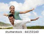 happy hispanic couple in love, man giving piggyback to woman - stock photo