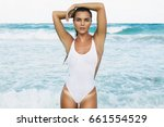 sexy woman in white swimsuit is ... | Shutterstock . vector #661554529