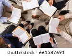Stock photo elevated view of people sitting on chair in circle reading books 661587691