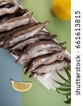 Small photo of Freshly frozen capelin lies on a white plate on a light blue-green background.