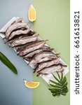 Small photo of A minimalistic composition with a freshly frozen capelin on a blue-green background.
