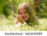 little girl lies in the grass... | Shutterstock . vector #661644589