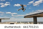 Small photo of A man is jumping from roof to roof. Parkour. Active lifestyle. Courage and Adrenaline. Roofer