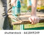 man with electric jigsaw works... | Shutterstock . vector #661849249