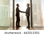 Small photo of Two businessmen shaking hands standing at big window with urban cityscape, confident business partners handshaking in office, forming good relations, establish partnership, support, help. Side view