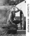 Small photo of Black and white image of sad woman sitting at broken car and trying to change flat tire
