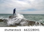 A Fisherman Stands On A Rock...