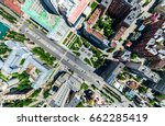 Small photo of Aerial city view with crossroads and roads, houses, buildings, parks and parking lots, bridges. Helicopter drone shot. Wide Panoramic image.