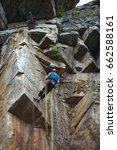 Small photo of Two climbers work on the route entrenched on a rocky ledge.