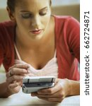 Small photo of Woman text messaging on PDA phone