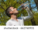 man is drinking water against a ... | Shutterstock . vector #662760931