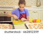 girl slices pepper for pizza... | Shutterstock . vector #662852359