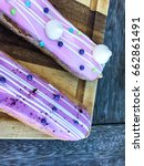 Small photo of Delicious eclairs on wooden table, top view. Raspberry Eclair in french traditional.