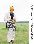 Small photo of Industrial climber in helmet and white uniform preparing for work. Professional worker getting ready. Alpinist equipment