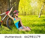 Small photo of Girl traveling bicycle in summer park. Bicyclist has rest near bike. Cycling is good for health in summer and spring. Girl is waiting for guy on date. Happy resting teenager.