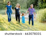 cheerful family in a park  dad  ... | Shutterstock . vector #663078331