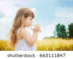 the child holds a glass of... | Shutterstock . vector #663111847