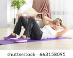 mature woman doing sit ups at... | Shutterstock . vector #663158095