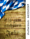 """Small photo of bavarian tablecloth on wood with the sentence """"Until next year"""" in German"""