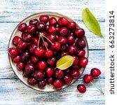 fresh cherry on plate on wooden ... | Shutterstock . vector #663273814