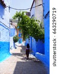 Small photo of Allay of Chefchaouen, Morocco, the striking, variously hued blue-washed old town. Medina of Chefchaouen, Morocco. Brunette woman in a long dress walking alone on the blue streets of Chefchaouen