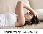 Small photo of Woman lying on sofa having headache. Stressed girl suffering of fatigue, migraine, trying to cope with nervous tension, worries because of problems, unwanted pregnancy, negative thoughts and emotions
