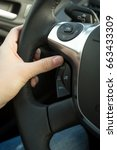 Small photo of Closeup of female driver adjusting cruise control system on steering wheel