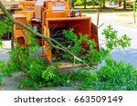 Small photo of Landscapers using chipper machine to remove and haul chainsaw tree branches