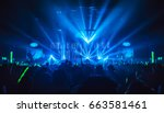 Stock photo silhouette in night club under blue rays beam and young people holding light saber enjoying at 663581461