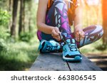 Small photo of Female runner tying shoe lace in the park. Healthy lifestyle.