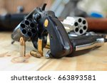 pistol and bullet on table... | Shutterstock . vector #663893581
