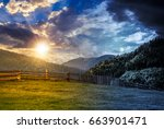 day and night time change concept. wooden fence through the grassy meadow in mountains. beautiful Carpathian countryside landscape with cloudy sky with sun and moon - stock photo