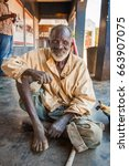 Small photo of LILONGWE, MALAWI - SEPTEMBER 05 2009: An old African Malawian man in ragged clothing sits outside a dilapidated shop in Malawi.