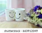 Small photo of Two happy cups with dries flowers on the bed. Concept about love and relationship
