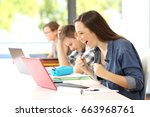 Small photo of Side view of an excited student receiving good news on line beside another sad classmate in a classroom