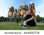 Stock photo pretty gil sitting in front of berlin cathedral at beautiful sunset wearing sunglasses relax and 664000729