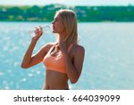 young girl drinks water | Shutterstock . vector #664039099
