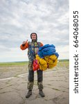 Small photo of Happy skydiver is standing on the airfield with a parachute in his hands - the joy after the first jump. Wide angle of shooting.