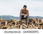 man sitting on the firewoods.... | Shutterstock . vector #664083091