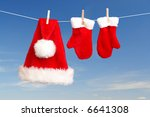Red santa claus hat and pair of gloves drying in the open air hanging on clothes line affixed with wooden pegs - stock photo