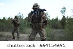 Small photo of Military troop prepared for fight aiming with guns on the field.