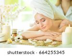 girl lying down on a massage bed | Shutterstock . vector #664255345