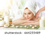 girl lying down on a massage bed | Shutterstock . vector #664255489